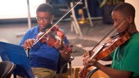 Photo of two boys playing violins