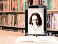 A photo of a photograph on a tablet propped up on a book. The tablet image shows a woman looking down at the book.