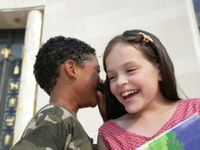 Boy whispering into a girl's ear both smiling