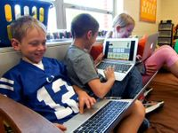 Three kids sitting in class on a big futon each with a laptop
