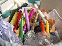 A photo of a classroom garbage can, with wadded up papers, pencils, and markers.