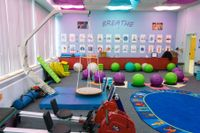 A colorful classroom with light purple walls, blue and purple cloths covering the ceiling lights, a swing set, bouncy balls to sit on, and rowing exercise equipment.