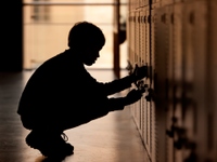 A photo of a male student in front of his locker.