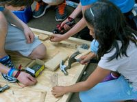 Girl using a hammer and another student using a drill