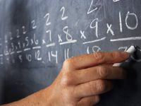 Hand holding chalk writing multiplication problems on a blackboard