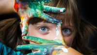 Photo of a girl with paint on both hands