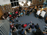 a photo of a group of high school students sitting on the floor in a discussion with their teacher.