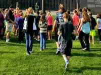 Students walking on a grassy field