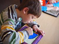 A boy is hunched over a rectangular device on his desk, drawing.