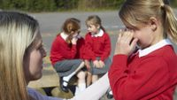 A teacher helps a young girl calm down to deal with a stressful situation.