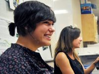 Two young women are sitting in a classroom, one smiling widely.
