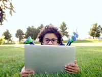 Boy laying on the lawn peeking out over his laptop