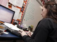 A side profile, closeup of a young, female teacher typing while looking at her laptop. She's sitting in her classroom toward the front of the room next to a whiteboard.