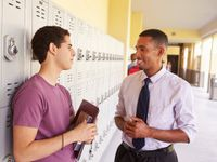 A male teacher and teenage boy are smiling, talking in a school hallway. The student is leaning against his locker, holding a folder and book.