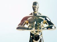 A closeup of an Oscar award, a small, golden statue of a standing naked man. His hands are in front of him, below his chest, holding a wreath.