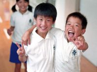 Two young, smiling boys standing in a school hallway wearing white polo shirts have an arm around each other's shoulder and are making the peace sign with their other hand.