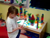 A young girl with long hair in a white t-shirt and blue shorts is sitting at a kid-sized table with colorful, clear, Lego-like building pieces. On the table are variations of different towers.