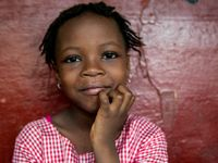 A closeup of a young girl, close-mouth smiling, with her chin resting on her right hand.