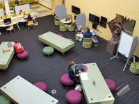 Teachers and students are sitting in a uniquely designed and furnished classroom with different sitting chairs and different sized and shaped tables.