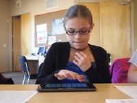 A young girl is sitting at a table in a classroom, working on a tablet.