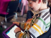 A closeup of the side of a young boy sitting in class, smiling, working on his tablet.