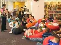 A group of about 20 young children are sitting and laying down on bean bags in a library. They're listening to a teacher standing in from of them and talking to them.