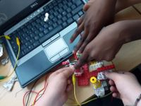 A closeup of two pairs of hands making something out of legos and tin foil over a desk, laptop, and red, yellow, and black wires.