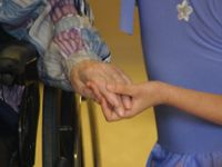 photo of a young person and an elder holding hands