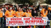 """A large group of special needs students are marching in the street, proudly raising their arms, cheering, and holding a large sign that says, """"Hudson High School Special Olympians -- Multi-State Champs in Soccer and Softball."""""""