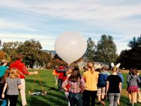 A classroom of kids and teacher out on the field getting ready to release a weather balloon