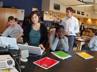 Three students are sitting at a long, black table in a large classroom. Two are on laptops, and one has her face in her hands with her elbows on the table. More students are sitting behind them at desks and a teacher is standing behind them.