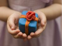 A closeup of a young kid's hands cupping a blue Play-Doh boxed gift with orange Play-Doh ribbon and a red Play-Doh bow.