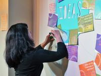 """A teacher is writing on a piece of paper against the wall. The word """"Ideas"""" is written on the wall. Pieces of paper with questions like, """"How would you define open education?"""" surround the word """"Ideas,"""" and people's responses are written on them."""