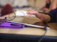 With a blurred background, a student's hand is highlighted hovering over a tablet.