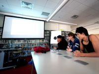 Three high school students are sitting at a long table with a projector in front of them and bookshelves lined across the wall next to them.