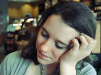 A closeup of a young women in a green shirt resting her head on her hand. The background, a coffee shop, is blurred.