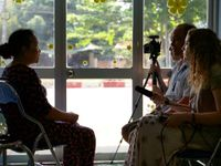 Three adults are sitting across from an old woman in a classroom, filming her. One of them is holding a camera on a tripod, and another is holding a long microphone.