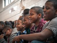 A closeup of a large group of young, black kids smiling, sitting in bleachers in a multipurpose room