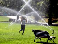 photo of a woman running through the sprinklers