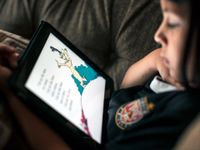 A closeup of a kid sitting, reading Dr. Seuss on a tablet.