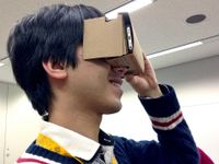 A teenage boy is holding a Google Cardboard viewer up to his eyes, a cardboard box with his smart phone inside of it, looking into it as if it were binoculars or a camera.