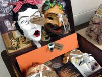 Four masks in the style of classical Greek theatre are displayed in an open box alongside images of Greek masks.