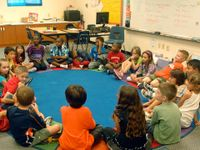 A group of young elementary students are sitting in an oval on their classroom floor on a blue circular rug with a colorful border.