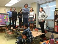 Six preteen students are standing on their classroom desks, smiling, and one student is sitting.