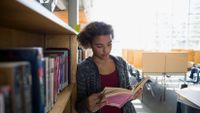 A young, teenage girl is leaning against a library shelf, reading a book.