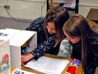 Two young women are squatting by a table in a classroom; one of them is reaching into a cardboard box that's part of a display.