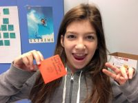 """A young girl with long, brown-red hair is looking directly at the camera, smiling. She's standing in front of a classroom wall making a peace sign with her left hand and holding up an orange post-it in her right hand that says, """"Computer aided design is a"""