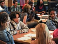A group of ten high school students are in a library sitting at tables and talking to each other.