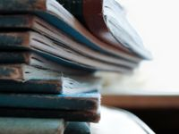 A closeup of a stack of blue, old, faded books on a circular table.