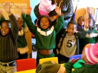 A group of eight young, elementary students are standing by their classroom desks with their arms raised in the air, talking. An adult is standing by them, holding a baby.